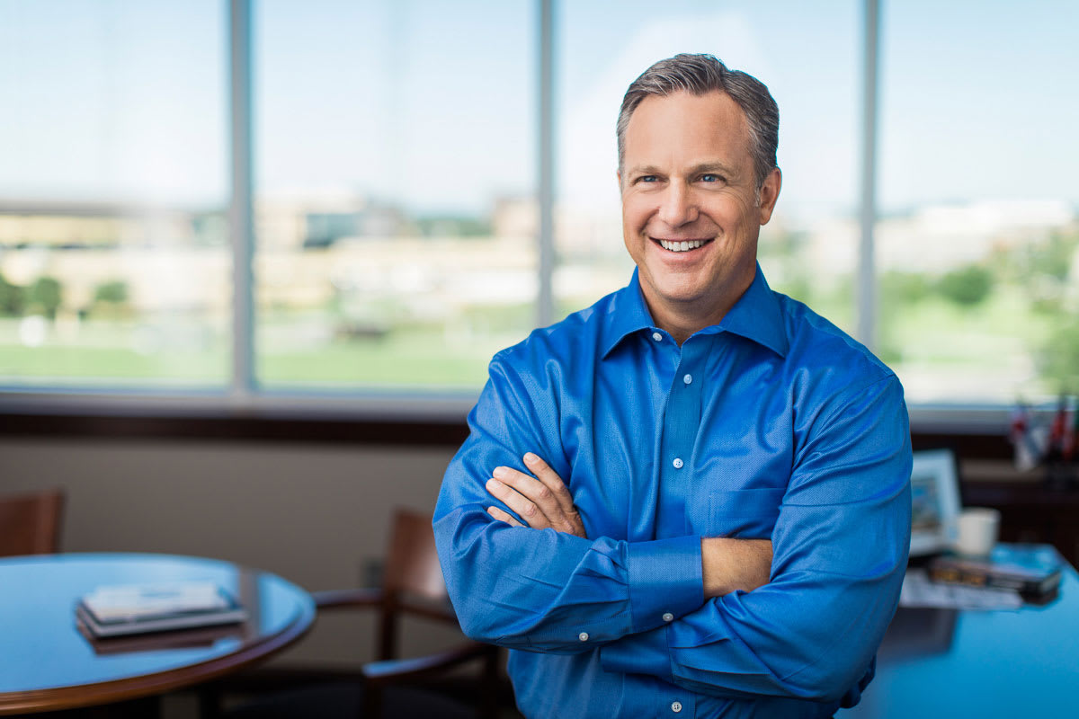 Home Instead's Jeff Huber Smiling in office in front of windows