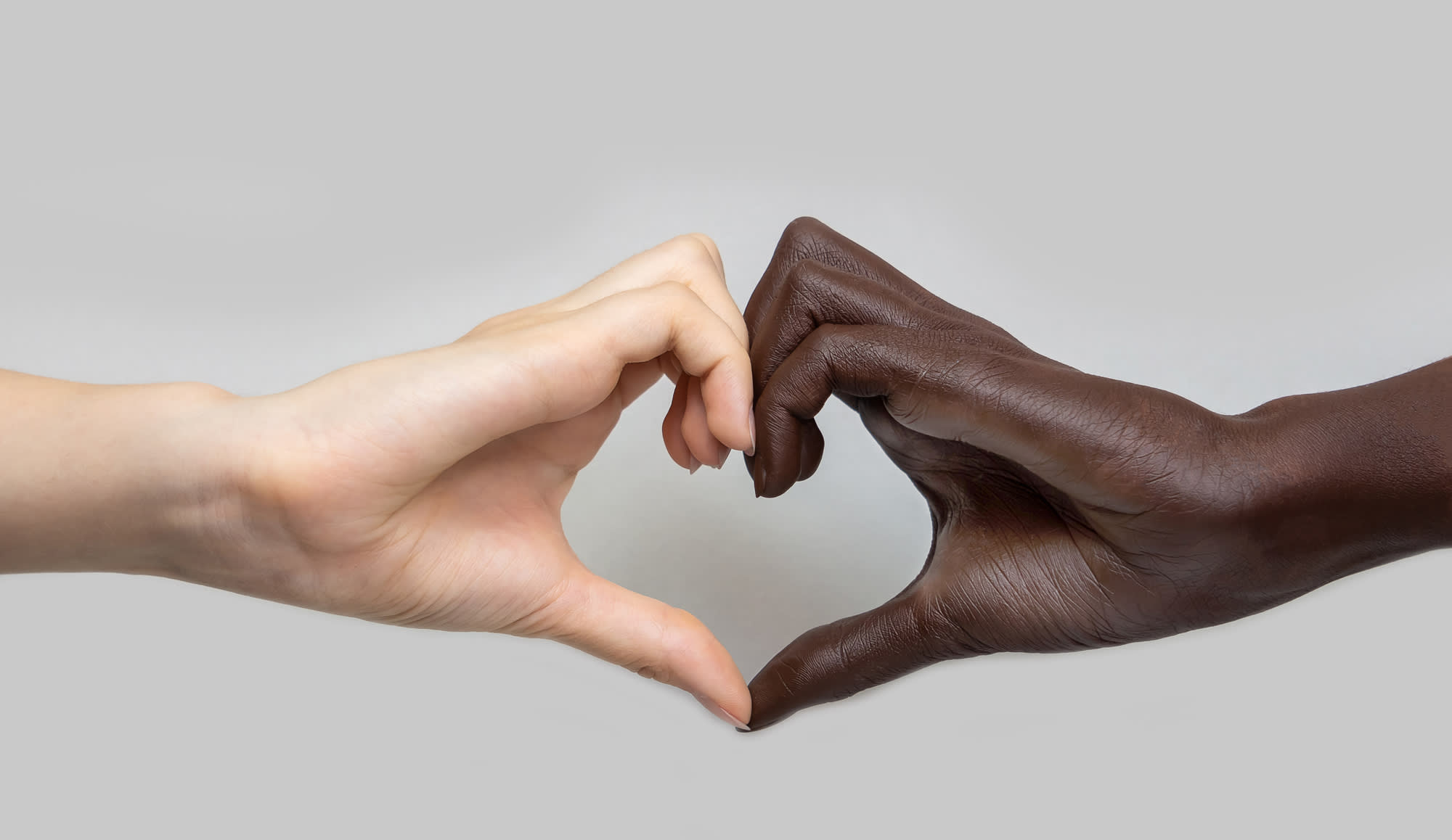Black and white heart-shaped hands on a grey isolated background. The concept of inter-racial friendship and respect, the fight against racism