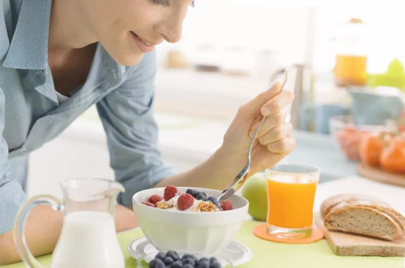Middle-aged woman eating a healthy breakfast