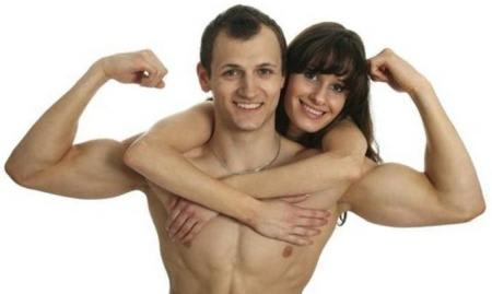 Young woman hugs her muscular boyfriend
