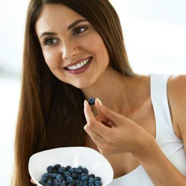 Attractive Young Woman Eating Ripe Fresh Blueberries