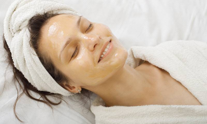 Young woman with honey mask on her face