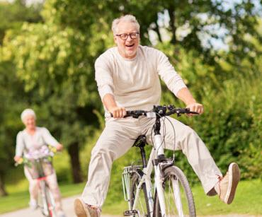 Happy Senior Couple Cycling In The Park