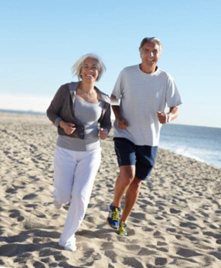 Elderly couple jogging on the beach