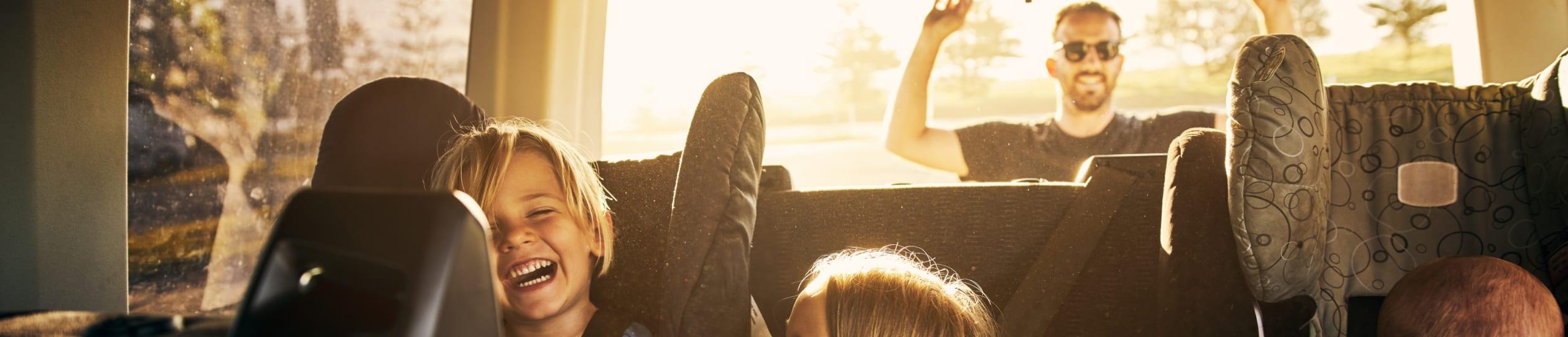 Drei lachende Kinder in einem Auto mit ihrem Vater