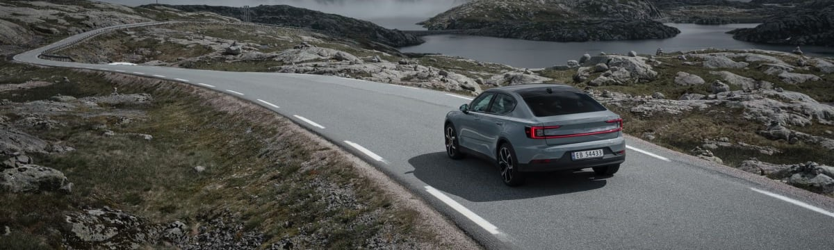 A Polestar drives on a road in nature