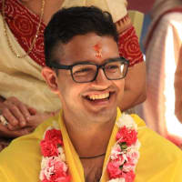 Akhil Jobanputra smiling and wearing a yellow shawl and a garland of red and pink flowers.