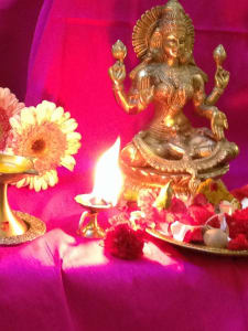 Altar with figurine, flowers, and oil lamp.
