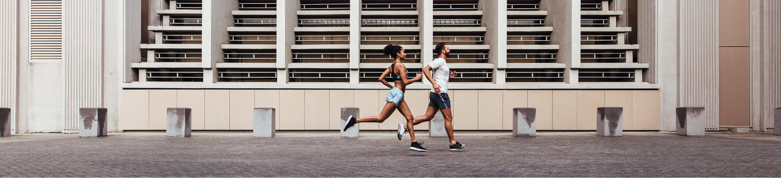 Couple jogging near bleachers