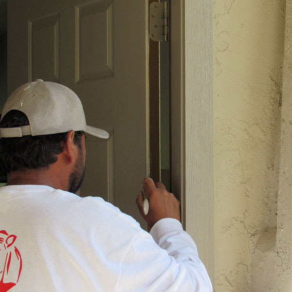 Using a brush, our painter adds the finishing touches to a front door here in Gilbert, AZ.