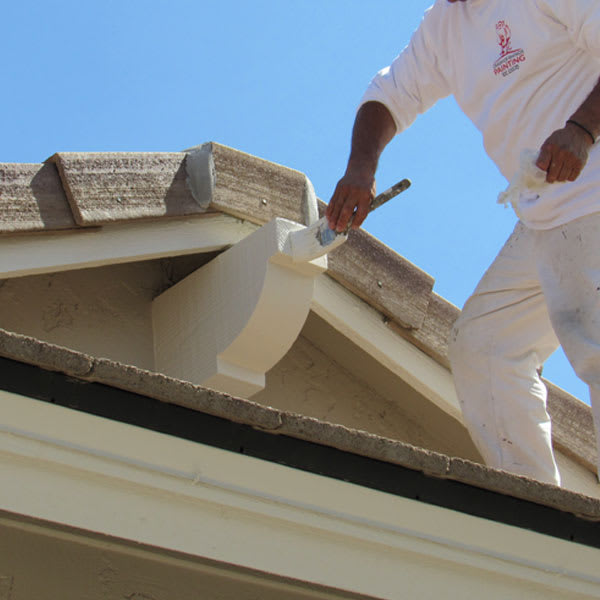 Our painters in Gilbert, AZ never lose sight of the small details, as our painter climbs the roof to brush a decorative fixture.