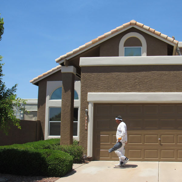 A Crash of Rhinos painter walks in front of a freshly painted home here in Phoenix, inspecting his work as part of our quality assurance process.