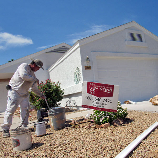A Crash of Rhinos painter gets paint from a bucket as they prepare to repaint this home in Mesa, Arizona.