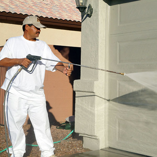 Our painter uses a pressure washer to thoroughly clean off the garage door of a home here in Phoenix, Arizona.