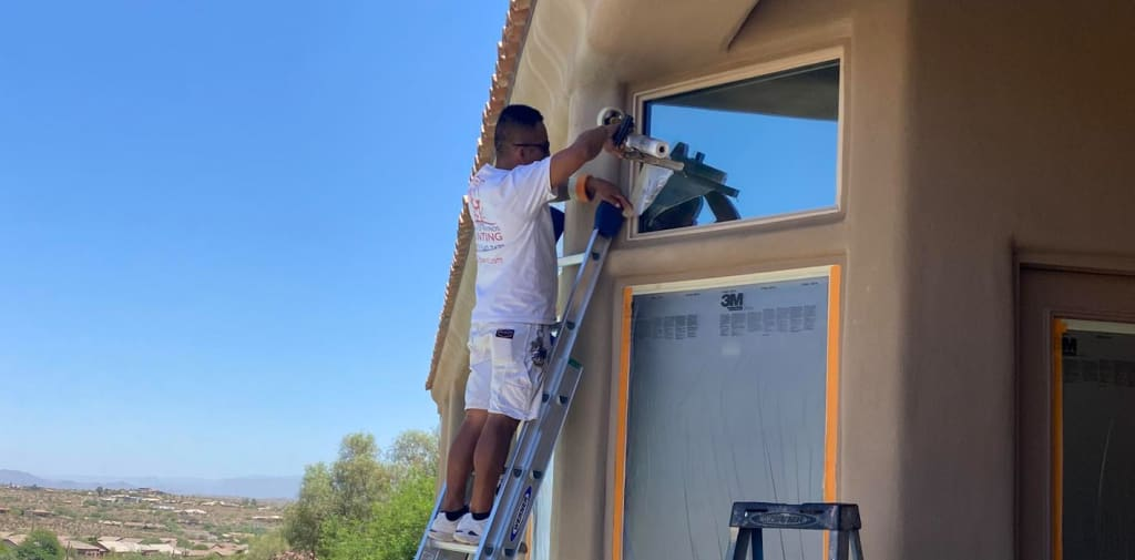 Standing on a ladder, our painter begins masking for paint in Phoenix, AZ, ensuring the windows are fully protected.