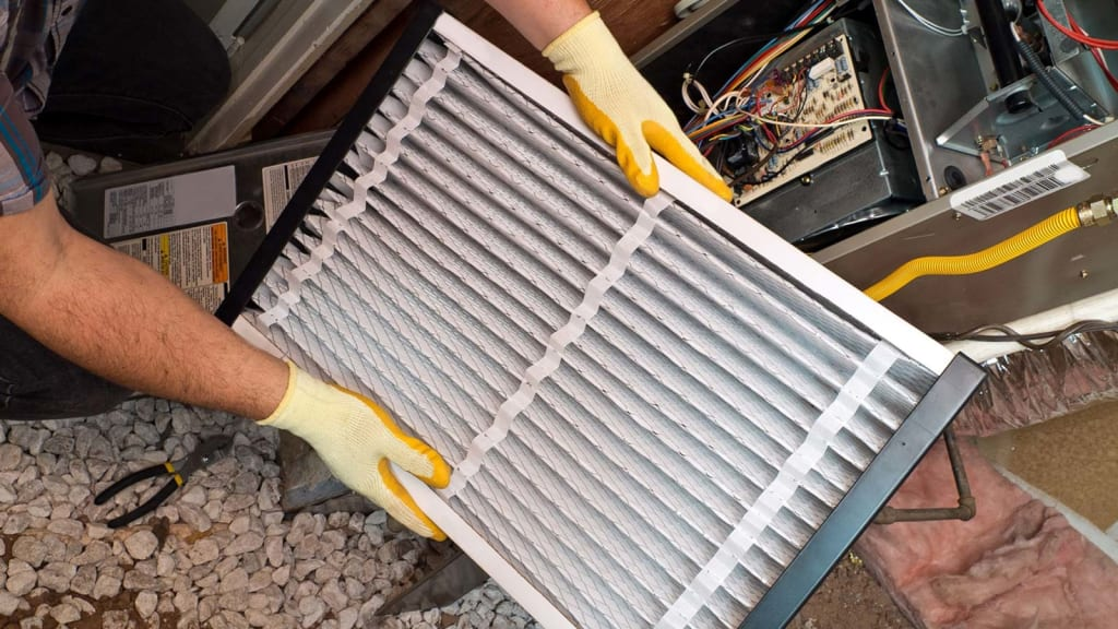 A King technician visually inspects a furnace filter after cleaning it, ensuring that it's ready to protect the furnace.