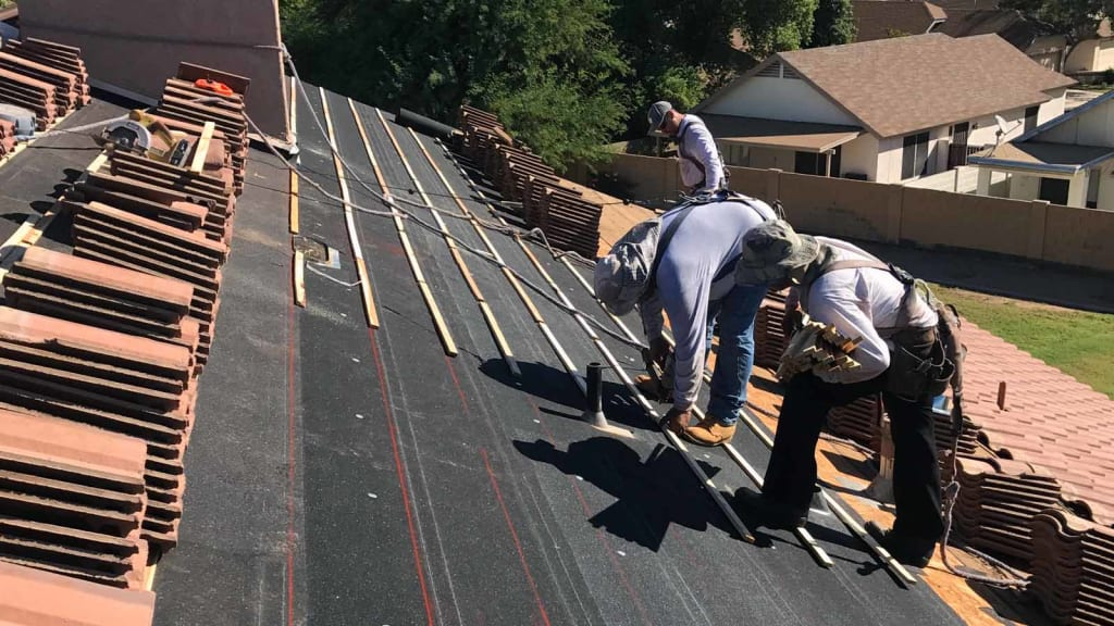 KY-KY's roofers prepare this roof's underlayment for new tiles, which are stacked above and below them.