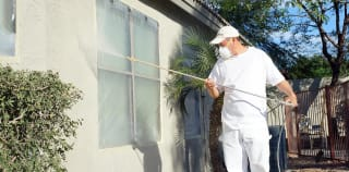 With the windows masked and taped, our painter begins the paint application process using professional-grade painting tools.