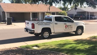 A KY-KO Pest Prevention truck sits parked on the street outside this Phoenix-area home.