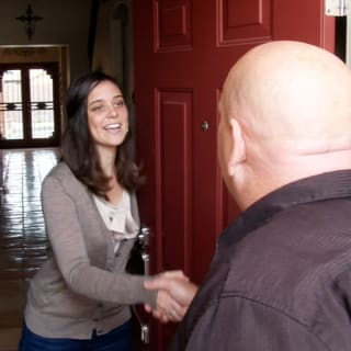 Mike Ricker, the owner of Crash of Rhinos, shakes the hand of a local homeowner ahead of their free inspection.