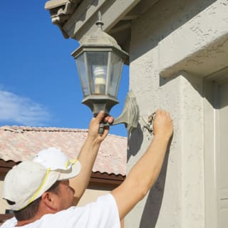 Having completed the job, our painter re-attaches a light fixture to the outside of the home.