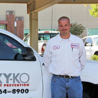 A trusted KY-KO Pest technician stands in front of a KY-KO service vehicle before heading out to their next inspection.