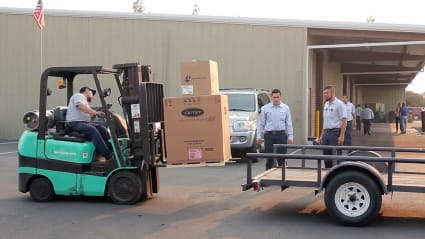 An Allbritten technician uses a forklift to lift a new Carrier air conditioner onto a flatbed truck.