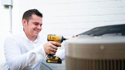 Having just completed a Fresno AC tune-up, our technician uses a cordless drill to fasten the condenser back together.