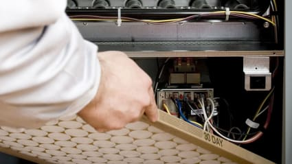 Having just completed preventative maintenance for the system, our technician inserts a clean furnace filter back into the system.
