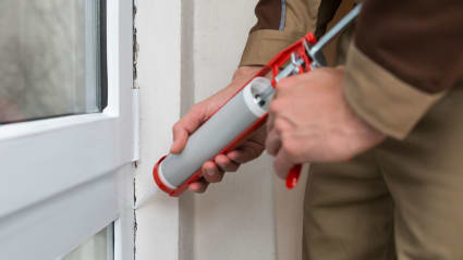 A KY-KO pest technician uses a caulking gun to apply caulk around this home's door frame, sealing pests out of the home.