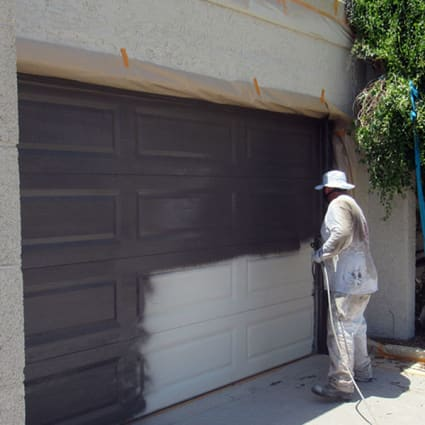 Our painter sprays paint onto a garage door here in Phoenix, Arizona, completely transforming its color and look.