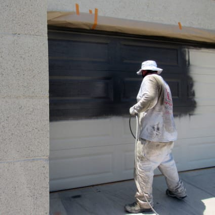 A Crash of Rhinos painter paints the garage door in the chosen accent color, making sure that the coat is complete.