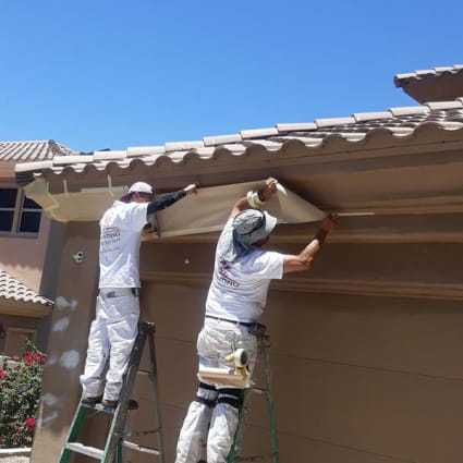 With this Glendale home completely painted, two of our painters carefully remove the masking and tape protecting the accent trim.