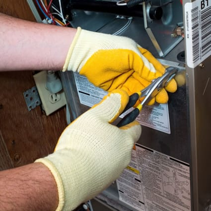 During a furnace tune-up in Chicago, our tech uses pliers to access a gas furnace to start the cleaning process.