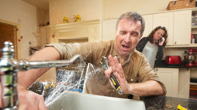 A homeowner attempts to fix their own kitchen sink, resulting in water spraying them in the face.