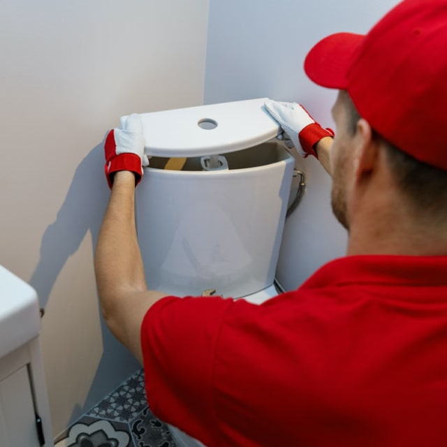 One of our plumbers replaces the top of a toilet tank after adjusting the water level for a homeowner here in Chicago.