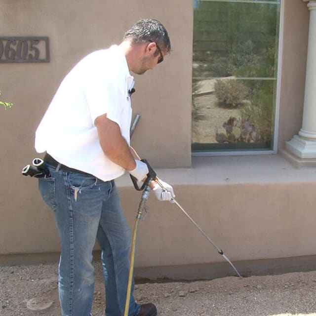 A KY-KO termite treatment specialist here in Scottsdale, AZ applies termiticide to a trench.