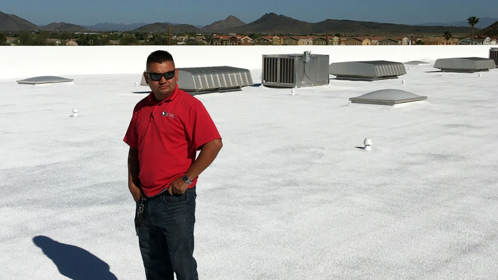 A KY-KO roofing specialist surveys the top of this office building's foam roof after completing their quality assurance review.