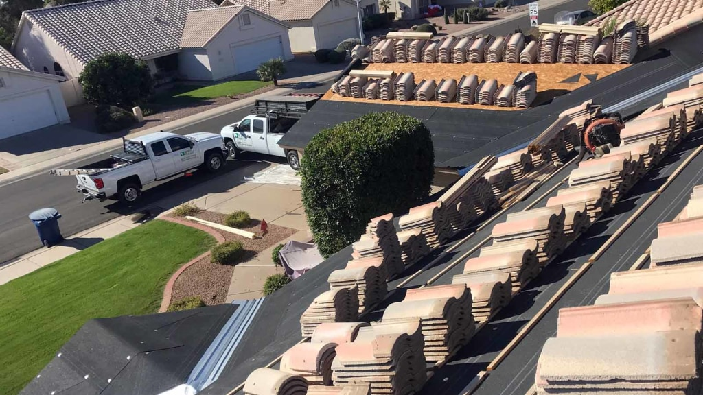 The view from a roof of a Phoenix roof replacement project, where two KY-KO trucks sit parked into the driveway.