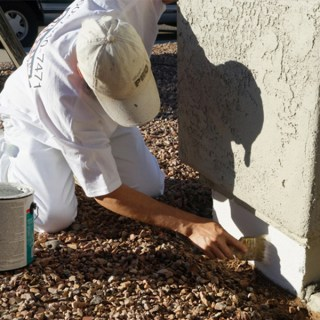 Our painter applies primer to the stem wall of this home, creating an ideal surface for the paint to adhere to.
