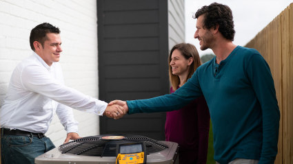 Having just completed AC installation, our technician meets with the two homeowners to review their new system.