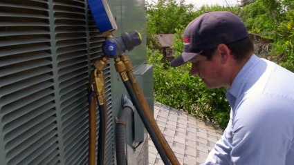 Our HVAC technician works on top of this Fresno home, thoroughly inspecting this rooftop air conditioner.