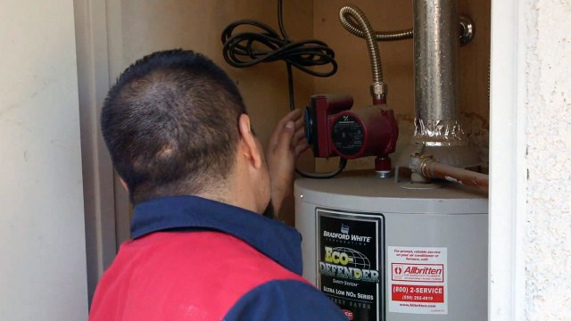 Our plumber inspects the water heater in a local home as part of a plumbing service call.