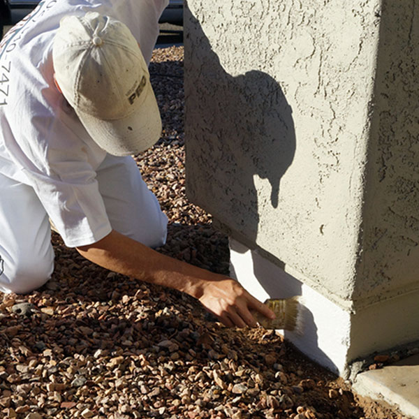 A painter brushes protective DRYLOK onto the stem wall of this pillar, ensuring the paint above is protected from ground moisture.