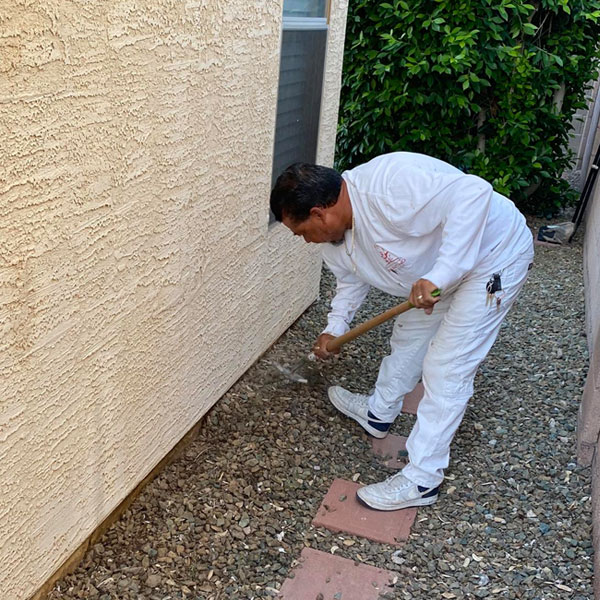 Our painter uses a rake to pull landscaping rocks away from the stem wall of the home, allowing us to access it for prep and paint.
