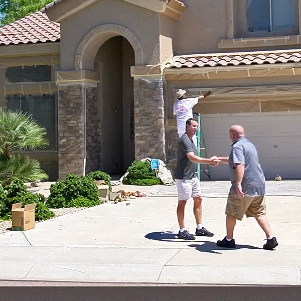Our owner, Mike Ricker, shakes the hand of a local homeowner and updates them on the state of their current painting project.