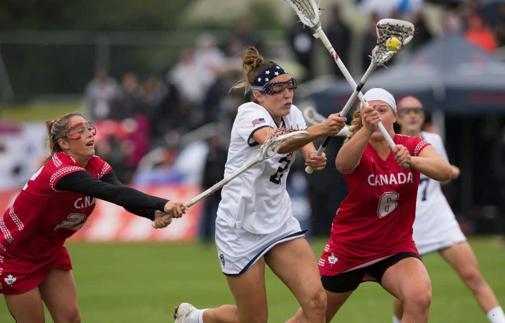 Team USA's Taylor Cummings challenges with Canada's Taylor Gait (L) and Kay Morissett during the World Cup Final at the 2017 FIL Rathbones Women's Lacrosse World Cup, at Surrey Sports Park, Guildford, Surrey, UK, 22nd July 2017.