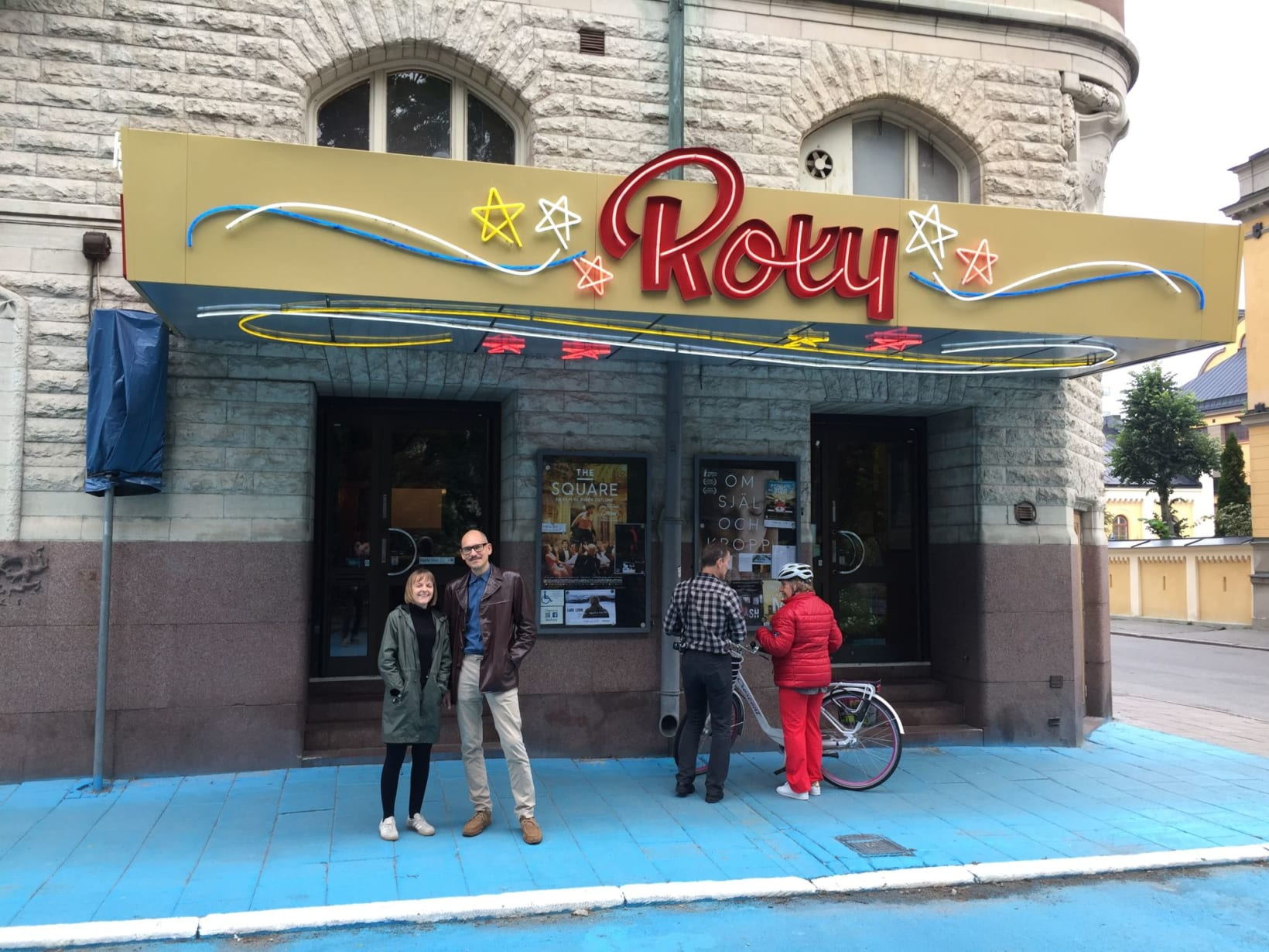 Photograph of Amy and Bo stood outside the front of the Roxy Cinema, which has an illuminated sign with stars and Roxy in large red letters.