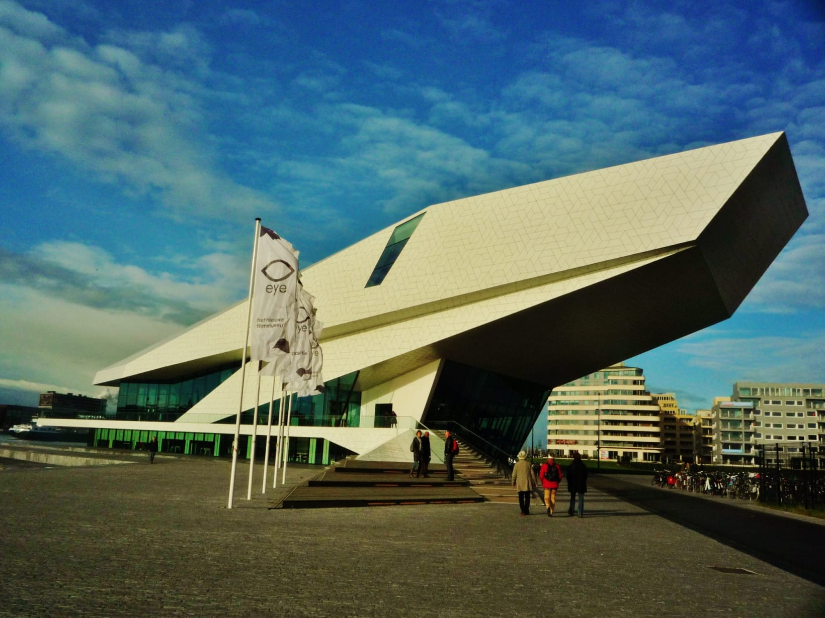 Photograph of the Eye Filmmuseum, against a blue sky. People walk towards the building.