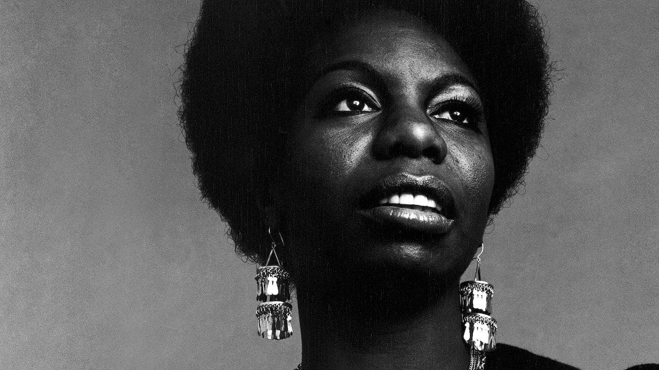 A powerful close up of Nina Simone, wearing large dangling earrings looking off into the distance.